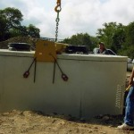 Lowering septic tank into hole